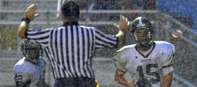 In a driving rain storm, Free State quarterback Kyle McFarland (15) keeps the ball to score late in the first half Friday, Aug. 31, 2012, in the season opener against Olathe Northwest at CBAC.