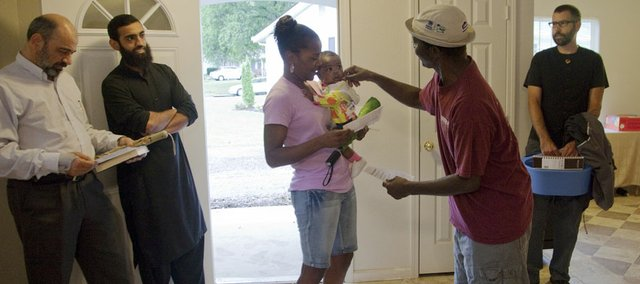 Hameed Yusuf, foreground right, greets 7-month-old Khloe and her mother Kamari Logan at the entrance of Yusaf and his family's' new Habitat home at 1933 Maple Lane, Saturday Sept. 1, 2012. Yusaf, his wife Asikat Hameed and their five children will live in the 80th Lawrence Habitat for Humanity house which was dedicated Saturday. Kamari helped build the Hameed home and is in line for a future Habitat Home in Lawrence.