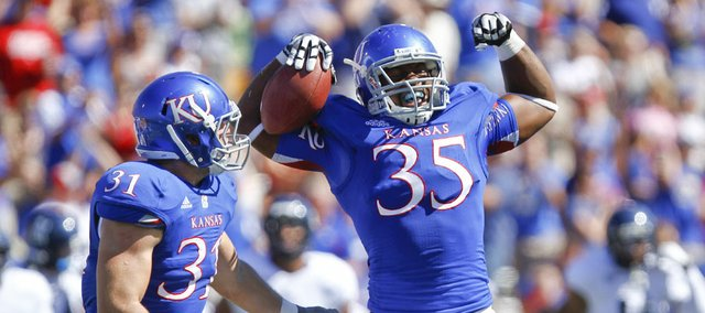 Kansas defensive end Toben Opurum (35) flexes his muscles next to linebacker Ben Heeney after sacking Rice quarterback Taylor McHargue and recovering a fumble on the play during the first quarter on Saturday, Sept. 8, 2012 at Memorial Stadium.