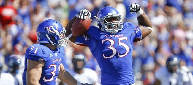 Kansas defensive end Toben Opurum (35) flexes his muscles next to linebacker Ben Heeney after sacking Rice quarterback Taylor McHargue and recovering a fumble on the play during the first quarte