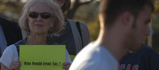 "Jean Shepherd, of Lawrence, holds a sign asking ""Who would Jesus tax?"" as people file into the Lied Center to hear Gov. Sam Brownback speak Monday."