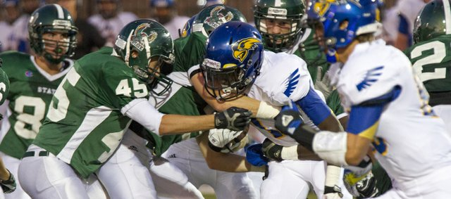 Free State defenders try to bring down Olathe South's Dresden Wilbur during their game Friday, Sept. 14, 2012, at FSHS.