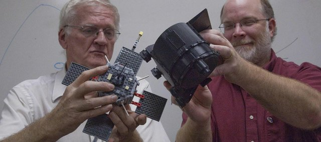 Professor Emeritus Tom Armstrong, left, holds a model of a satellite while Dr. Jerry  Manweiler handles a model of a device their company, Fundamental Technologies, makes that is mounted on the satellite that measures radiation rings around the Earth and how it affects cellphones. ABOVE, an image provided by the AP and NASA shows an image taken by the Voyager 1 spacecraft of a volcanic plume on the Jupiter moon Io. Voyager 1 is poised to soon leave the solar system.