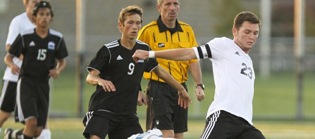 Lawrence High midfielder Justin Riley pushes the ball up the field past Olathe Northwest midfielder Brian Ness during the first half on Tuesday, Sept. 18, 2012 at Lawrence High School.