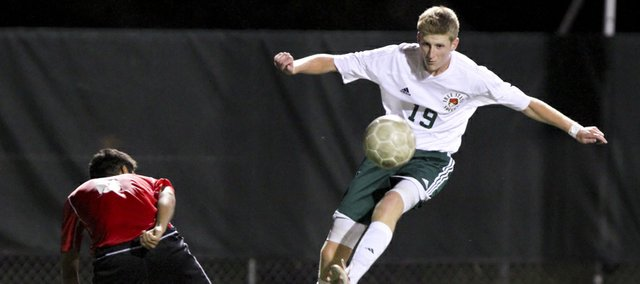 Free State midfielder Chris Allen sends the ball across the field to a Firebird teammate past Shawnee Mission North defender Miguel Molina during the second half on Thursday, Sept. 20, 2012 at Free State High School.