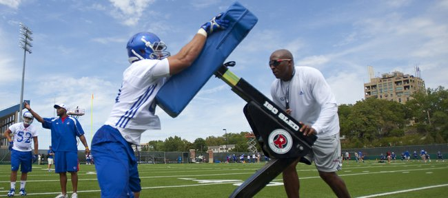 Kansas linebacker Anthony McDonald hits the sled before linebackers coach DeMontie Cross during practice on Thursday, Aug. 2, 2012. Nick Krug/Journal-World Photo