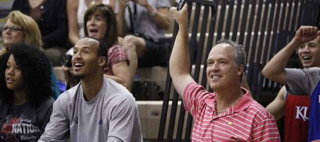 Doc Sadler, former Nebraska head coach, laughs next to Kansas guard Travis Releford as they watch the final minutes of the campers' basketball game against the counselors on Wednesday, June 13, 2012 at the Horejsi Center.
