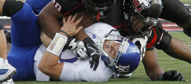 Dayne Crist (10) is sacked in the second half of KU's 30-23 loss to Northern Illinois Huskies Saturday, September 22, 2012, at Huskie Stadium in DeKalb, Ill. At top is left tackle Tanner Hawkinson.