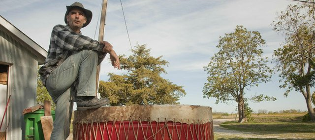 Cyrus Fillmore, who lives west of Baldwin, rests on a nearly six-foot drum he's making for the the Kansas City Chiefs.