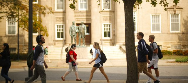 Kansas University Students walk on Jayhawk Boulevard past Lippincott Hall on Thursday. Fall enrollment numbers show a 2.7 percent decline in overall enrollment but a 5.3 percent increase in freshman enrollment.