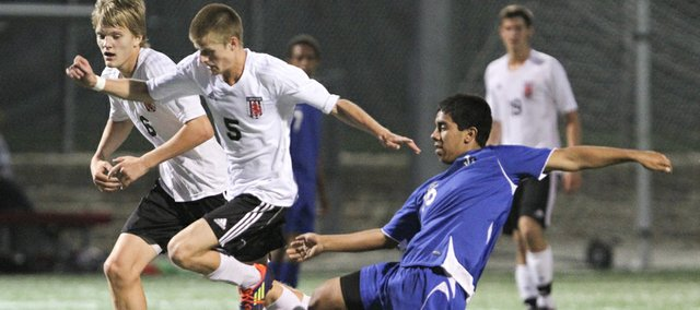 Lawrence High midfielder Gavin Fischer, center, breaks past Leavenworth defender Eduardo Rodriguez during the first half on Tuesday, Oct. 2, 2012 at Lawrence High School. At left is LHS forward Luke Matthews.