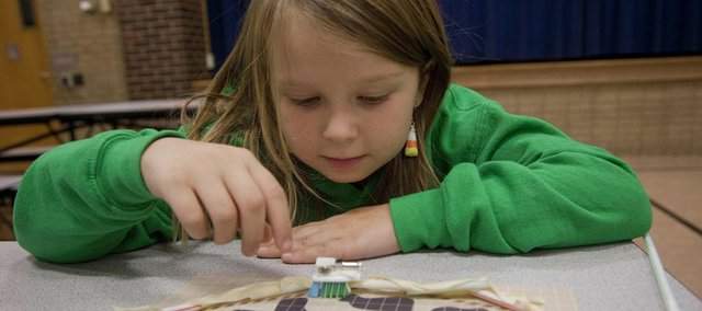 "Grace Adams, 7, a member of the Clinton Eagles 4-H Club, watches her ""eco-bot"" after it was deployed on a map representing an oil-spill area. At a National 4-H Week event at the former at Wakarusa Valley School, Grace and some of her fellow 4-H'ers learned firsthand about building robots that can be used to preserve and protect the environment."
