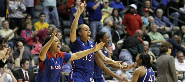 Kansas University's Tania Jackson (33), Natalie Knight (42), and other team members celebrate their 70-64 victory over Delaware in a second-round NCAA Tournament game on Tuesday in Little Rock, Ark. The Jayhawks advanced to the Sweet 16 for the first time since 1998.