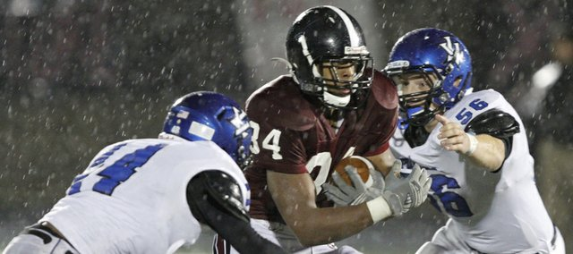 Tyrone Jenkins (34) looks for a hole in Friday's 46-26 Lions win over the Leavenworth Pioneers at LHS.