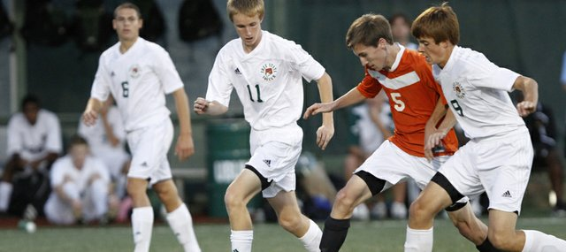 Free State soccer players Evan Smith (11), left, and Alex Heath (9) defend against Shawnee Mission Northwest&#39;s Tanner Sherman (5) in a 3-0 Firebirds loss on Tuesday, Oct. 16, 2012, at FSHS.