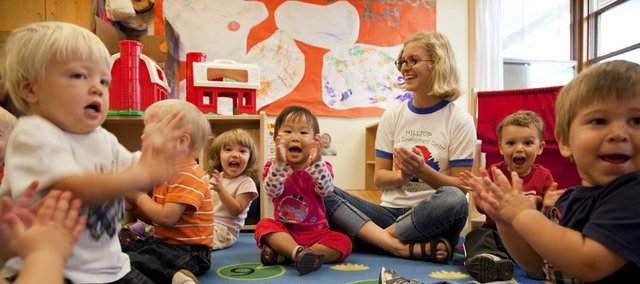 "Teacher Kelli Kuhlman sits among her 1-year-old students as they sing ""Wheels On the Car"" at Hilltop Child Development Center. Hilltop will celebrate it's 40th anniversary this weekend."