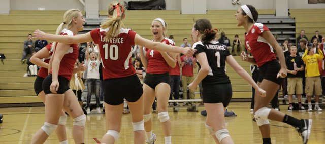 The Lawrence High volleyball team celebrates a set victory during the city showdown against Free State on Thursday at FSHS. The Lions took down their rivals, 3-1.