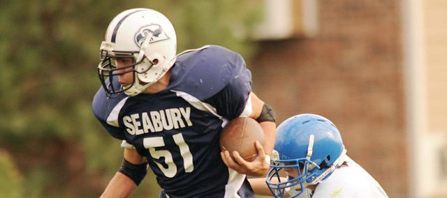 Kansas School for the Deaf's Tyler Foster, right, tries to stop Seabury's Fischer Almanza (51) on Wednesday, Oct. 17, 2012, at Seabury.
