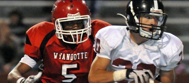Lawrence High's Will Thompson (20) snags a reception to set up a touchdown in the second quarter against Wyandotte on Friday, Oct. 19, 2012, in Kansas City, Kan.
