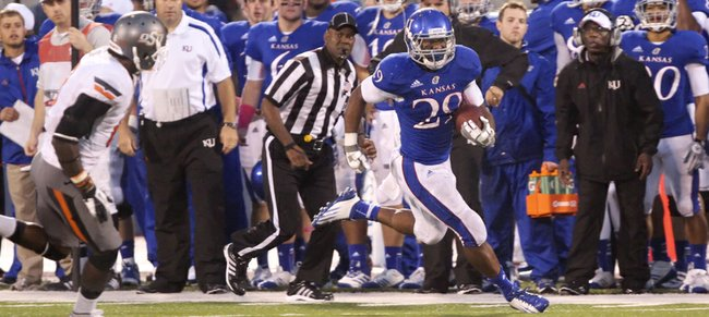 Kansas running back James Sims runs up the sideline past Oklahoma State safety Daytawion Lowe during the fourth quarter on Saturday, Oct. 13, 2012 at Memorial Stadium.