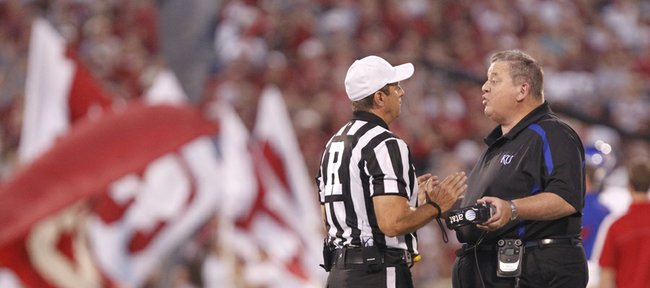 Kansas head coach Charlie Weis gives lip service to a game official as he disputes a call during the second quarter on Saturday, Oct. 20, 2012 at Memorial Stadium in Norman, Okla.