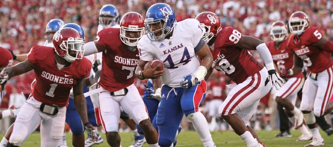 Kansas quarterback Michael Cummings is swarmed by Oklahoma defenders Tony Jefferson (1) Corey Nelson (7) and Chuka Ndulue (98) during the first quarter on Saturday, Oct. 20, 2012 at Memorial Stadium in Norman.