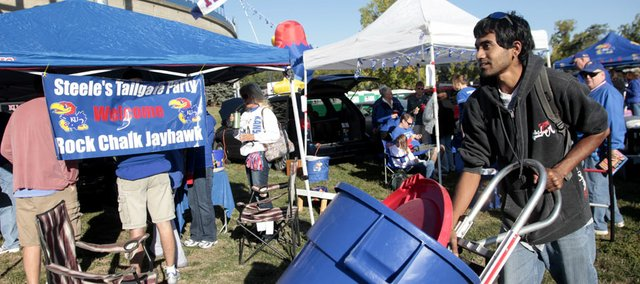 Nick Benson, a junior environmental studies manager at KU, spends some volunteer hours Saturday distributing recycling bins around the tailgating party area outside Memorial Stadium before the KU vs.Texas Tech game on Oct. 1, 2011.