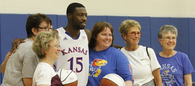 Senior Elijah Johnson, (15) has a photograph taken with women attending Ladies Night Out with Bill Self in Allen Fieldhouse Wednesday evening, Oct. 24, 2012. Women got a chance to run drills, get their photographs taken with and receive one-on-one instruction in basketball from members of the Kansas University men's basketball team and staff.