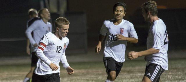 Lawrence High midfielder Johannes Reiber (12) celebrates his goal with teammates during their match against Topeka High, Tuesday, Oct. 23, 2012 at LHS.