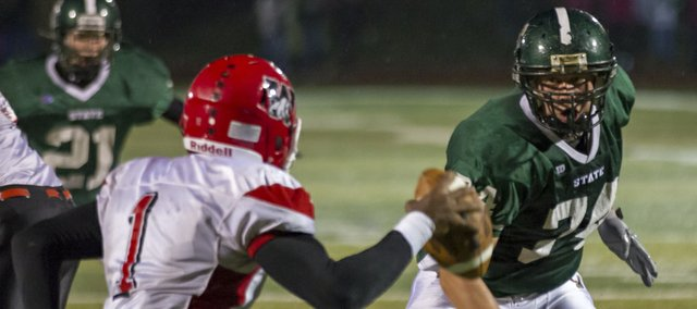 Free State's Cody Stanclift, right, sets his sights on Wyandotte quarterback Dimonic McKinzy (1) during their game Friday, Oct. 12, 2012, at FSHS.