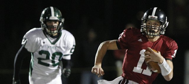 Lawrence High quarterback Brad Strauss breaks around Free State linebacker Keith Loneker during the first half on Friday, Oct. 26, 2012 at Lawrence High.