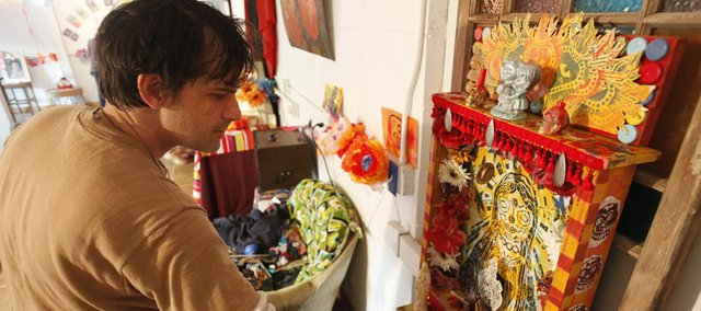 Lawrence artist Paul Punzo places items within an altar he created for a Día de los Muertos event Friday at the Lawrence Percolator, near Ninth and New Hampshire streets. Visitors are invited to create their own altars with pictures, mementos and decorations to pay homage to their loved ones.