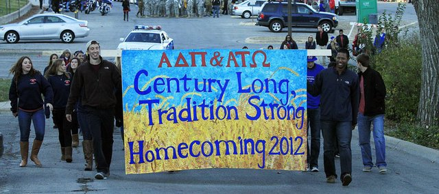 Fraternity members of Alpha Tau Omega Josh Cook, left, and Sean Jones carry a banner to help kick off the 2012 KU Homecoming parade Friday on Jayhawk Boulevard.