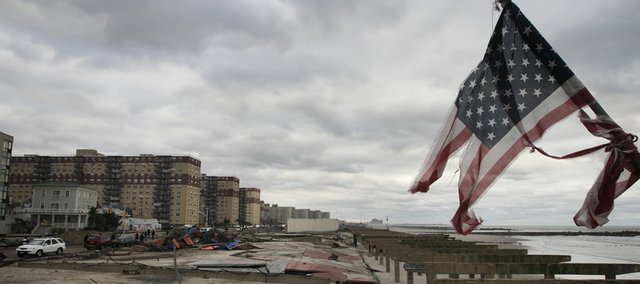 A damaged flag stands among the remnants of the boardwalk on Rockaway Beach the damage caused during hurricane Sandy, Wednesday, Oct. 31, 2012, in the Queens borough of New York.