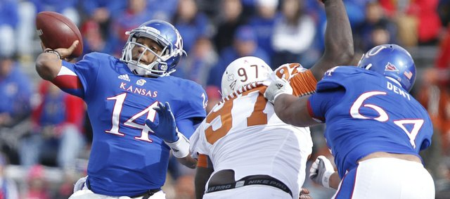 Kansas quarterback Michael Cummings heaves a pass as Texas defensive tackle Brandon Moore is fended off by KU lineman Randall Dent during the first quarter on Saturday, Oct. 27, 2012 at Memorial Stadium.