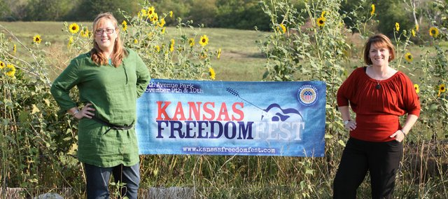 Keira Jones and Hope Corizzo stand next to a banner advertising Kansas FreedomFest, a two-day country music festival they organized to help honor veterans.