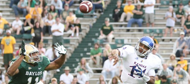 Kansas quarterback Michael Cummings is pressured by Baylor defensive end Terrance Lloyd during the third quarter, Saturday, Nov. 3, 2012 at Floyd Casey Stadium in Waco, Texas.