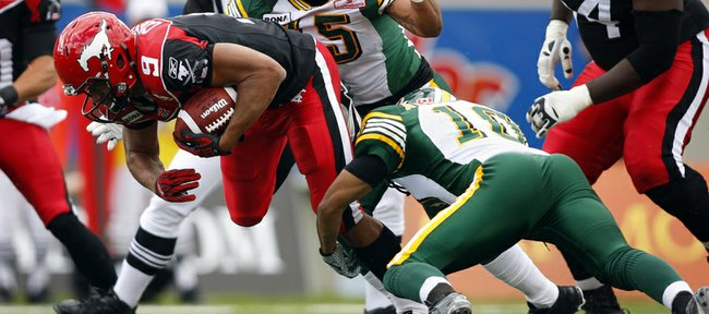 Edmonton Eskimos' Donovan Alexander, right, and Damaso Munoz tackle Calgary Stampeders' Jon Cornish during the first half of a CFL football game, Monday, Sept. 3, 2012, in Calgary, Alberta.
