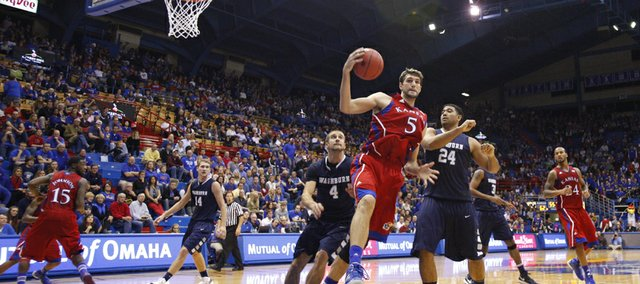 Kansas center Jeff Withey grabs a pass down low as he is guarded by Washburn defenders Jared Henry (4) and Zack Riggins (24) during the second half on Monday, Nov. 5, 2012 at Allen Fieldhouse.