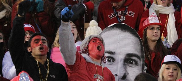 Lawrence High fans cheer on the Lions as a large cardboard head of senior Drake Hofer peeks out from the seats during the first half on Friday, Oct. 26, 2012 at Lawrence High.