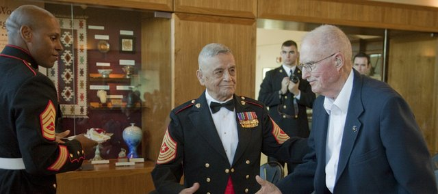 Jess Pacheco, retired Marine Corps Sgt. Major, center, reaches to shake hands with Lou Hammer, a retired sergeant, during the 237th birthday commemoration of the United States Marine Corps on Friday at the Dole Institute of Politics at Kansas University. Hammer was honored as the oldest Marine Corps veteran at the ceremony. At left is Gunnery Sgt. Dawud Hakim Jr., who presented the first piece of cake to Hammer.