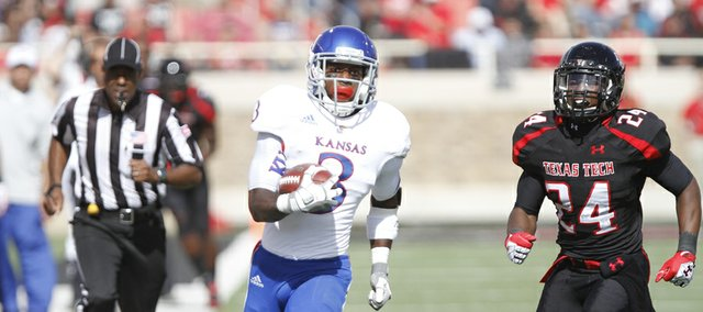 Kansas running back Tony Pierson heads up the sideline as Texas Tech defensive back Bruce Jones trails during the second quarter on Saturday, Nov. 10, 2012 at Jones AT&T Stadium in Lubbock, Texas.