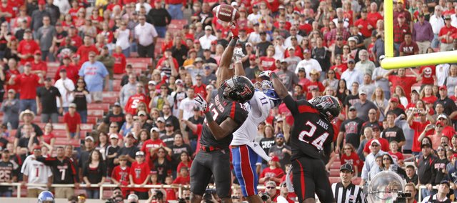 On the final play of the game safety D.J. Johnson (12) tips a pass in the endzone to Kansas receiver Tre' Parmalee (11) during the second overtime on Saturday, Nov. 10, 2012 at Jones AT&T Stadium in Lubbock, Texas. At right is Texas Tech defensive back Bruce Jones. The Jayhawks lost the game 41-34.
