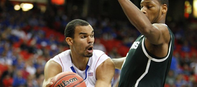 Kansas forward Perry Ellis looks to pass around Michigan State center Adreian Payne during the first half, Tuesday, Nov. 13, 2012 at the Georgia Dome in Atlanta.