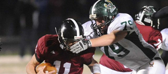 Free State's Riley Buller (79) gets comes in to tackle Lawrence High quarterback Brad Strauss (11) for a loss on Friday Oct 26, 2012. Free Sate won the game 28-14.