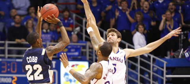 Kansas defenders Jeff Withey and Travis Releford extend to defend against a shot from Chattanooga guard Farad Cobb during the second half on Thursday, Nov. 15, 2012 at Allen Fieldhouse.