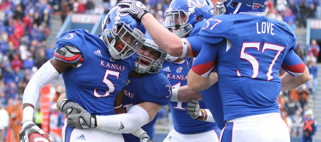 Kansas defenders celebrate with cornerback Greg Brown (5) after Brown's interception against Texas deep in the Jayhawks' territory during the second quarter on Saturday, Oct. 27, 2012 at Memorial Stadium.