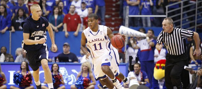Kansas guard Royce Woolridge pushes the ball up court past Washburn&#39;s Jeff Reid in the second half of the exhibition game, Tuesday, Nov. 2, 2010 at Allen Fieldhouse.
