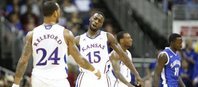 Kansas guard Elijah Johnson slaps hands with teammate Travis Releford after a breakaway bucket by Releford against Saint Louis in the first half of the championship game of the CBE Classic, Tuesday, Nov. 20, 2012 at the Sprint Center in Kansas City, Missouri.