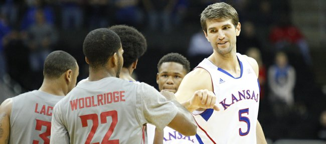 Kansas center Jeff Withey fist bumps his former teammate Royce Woolridge before tipoff of the CBE Classic, Monday, Nov. 19, 2012 at the Sprint Center in Kansas City, Missouri.